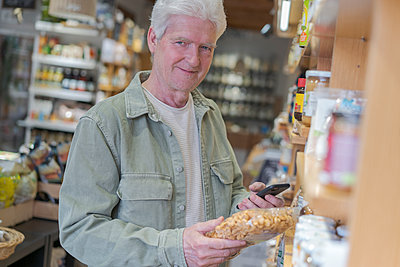 Portrait of senior man buying groceries in a small food store - p300m2179883 by VITTA GALLERY