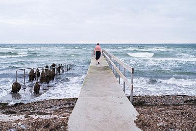 Man walking on pier - p312m1471409 by Viktor Holm