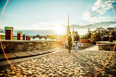 Caucasian tourists walking on cobblestone Leningrad street, Leningrad, Russia - p555m1413203 by Aleksander Rubtsov