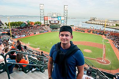 Man standing in baseball stadium in San Francisco, California, USA - p623m1125465f by Jerome Gorin