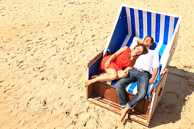 Couple in a hooded beach chair - p0452632 by Jasmin Sander