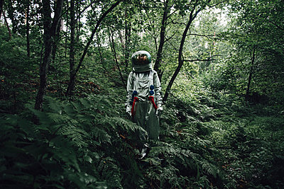 Spaceman exploring nature, looking at forest - p300m2030517 by Vasily Pindyurin