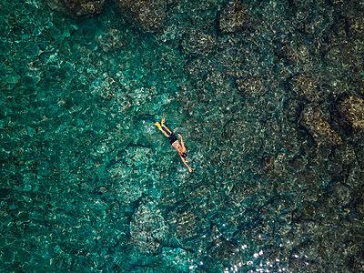 Indonesia, Bali, Man swimming in ocean at Amed beach - p300m2059327 by Konstantin Trubavin