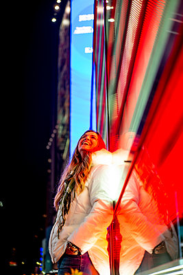 USA, New York, New York City, Portrait of young beautiful woman leaning on Times Square LED display at night - p300m2155691 by Oscar Carrascosa Martinez