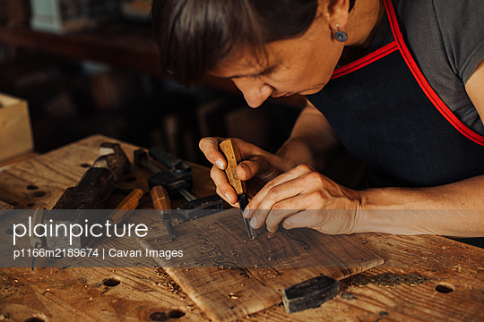 Woman engraving wooden panel using hand tools - p1166m2189674 by Cavan Images