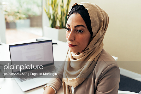 Businesswoman in office with laptop - p429m2237527 by Eugenio Marongiu