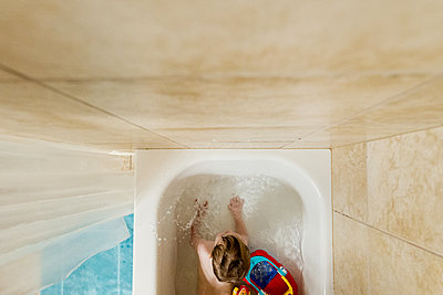 Overhead view of boy playing with toys in bath tub - p1166m1485275 by Cavan Images