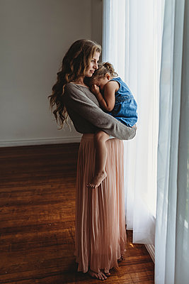 Full length view of mother and daughter cuddling by window in studio - p1166m2130800 by Cavan Images