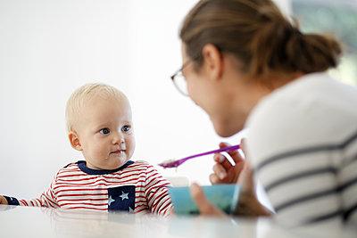Mutter füttert Kleinkind - p1258m2021280 von Peter Hamel