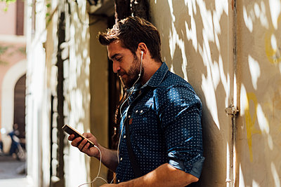 Man using earphones and smartphone outdoors - p300m2069404 von Boy photography