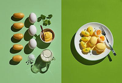 Directly above shot of eggs by ingredient in plate with fork on green background - p300m2143988 by Kai Schwabe