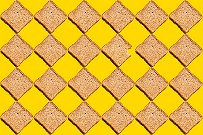 Pattern of slices of wheat bread against yellow background - p300m2198273 by Gemma Ferrando