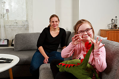 Mother with daughter on sofa - p312m2162046 by Phia Bergdahl
