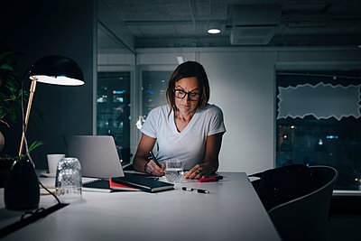 Female professional working late while sitting at desk in office - p426m2194754 by Maskot