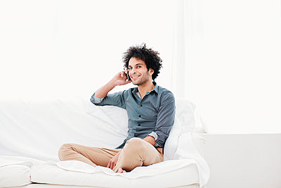 Man with Afro hairstyle using mobile phone - p586m1011161 by Kniel Synnatzschke