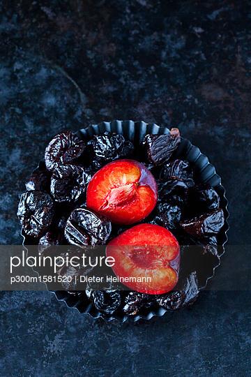 Fresh and dried plums in cake tin - p300m1581520 von Dieter Heinemann