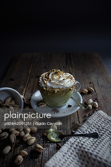 Cup of pudding with cream topped with pistachio bits - p924m2091251 by Guido Cavallini