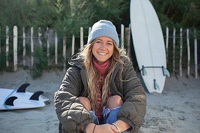 Portrait happy beautiful young female surfer sitting on beach - p1023m2262135 by Sam Edwards