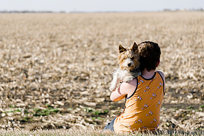 Boy sitting with his dog beside a corn field in the countryside. - p1166m2107774 by Cavan Images
