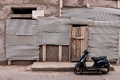 Morocco, Marrakesh, new motor scooter standing in front of a nailed barrack - p300m1032863 by Heike Skamper