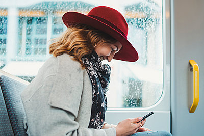 Happy young woman using cell phone in a tram - p300m2114136 by Francesco Buttitta