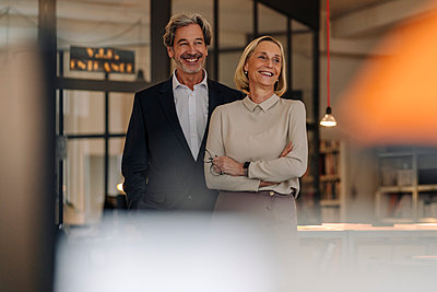 Portait of smiling businessman and businesswoman in office - p300m2156094 by Gustafsson