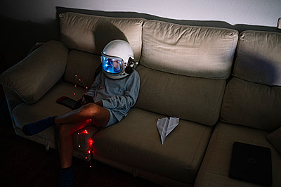 Boy wearing space helmet sitting with illuminated lighting equipment on sofa at home - p300m2221003 by Jose Luis CARRASCOSA