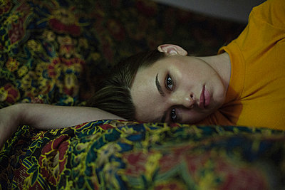 Portrait of beautiful young woman lying on bed - p301m1406371 by Nolwen Cifuentes