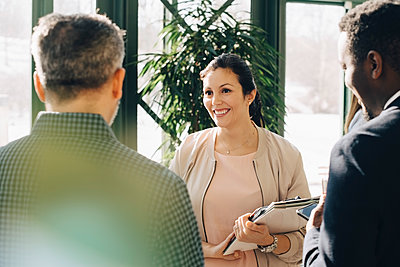 Smiling female entrepreneur discussing with male colleagues while standing in office - p426m1588635 by Maskot