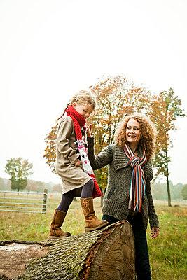 Mädchen balanciert über Baumstamm - p904m741710 von Stefanie Päffgen
