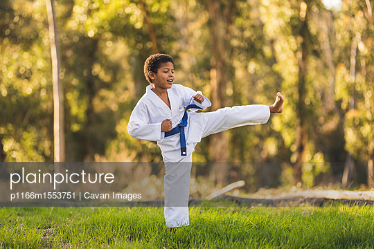 plainpicture - plainpicture p1166m1553751 - Boy practicing karate on gr... - plainpicture/Cavan Images