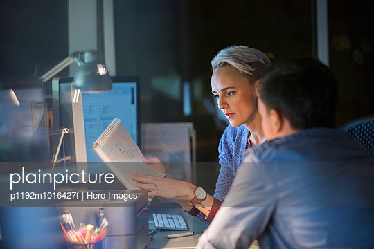 Business people working late in office - p1192m1016427f by Hero Images