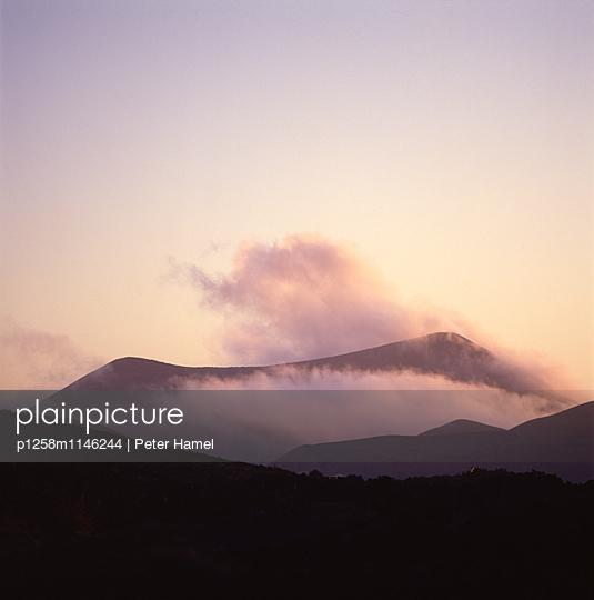 Wolkenfetzen zwischen Vulkanbergen auf Lanzarote - p1258m1146244 von Peter Hamel