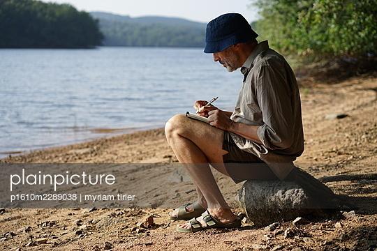 A man draws by a lake - p1610m2289038 by myriam tirler