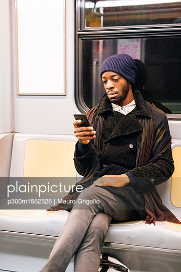 African american man with smartphone in metro - p300m1562526 by Mauro Grigollo