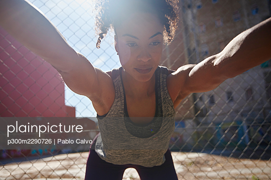 Sportswoman stretching while exercising in front of fence - p300m2290726 by Pablo Calvo