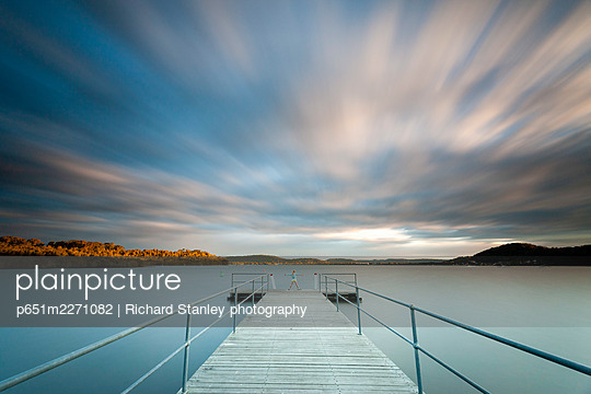 Long exposure of girl standaing on end of Kincumber Broadwater jetty.  Kincumber, Central Coast, New South Wales, Australia - p651m2271082 by Richard Stanley photography