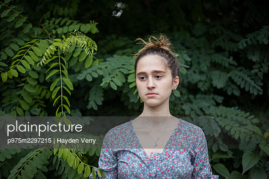 Young woman in front of a bush, portrait - p975m2297215 by Hayden Verry