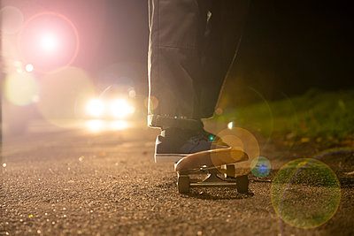 Young man skateboarding in headlights on roadside - p1023m2200951 by Himalayan Pics