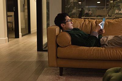 Businessman lying on sofa and using digital tablet - p1315m2041153 by Wavebreak