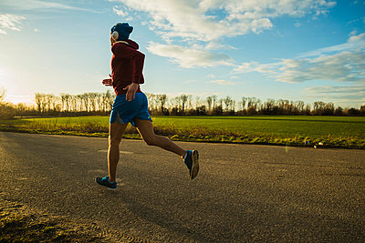 Germany, Mannheim, young man jogging on rural road - p300m1023034f by Uwe Umstätter