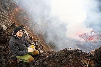 Africa, Democratic Republic of Congo, Virunga National Park, Man sittiing over Nyiragongo volcano crater - p300m2005431 by realitybites