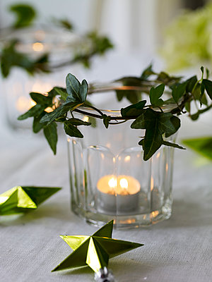 Lit tealight in jar with ivy and stars - p349m2167818 by Polly Wreford