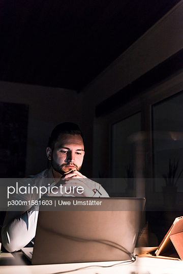 Portrait of businessman sitting at desk  in office at night looking at laptop - p300m1581603 von Uwe Umstätter