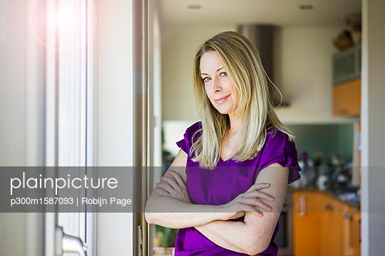 Portrait of smiling blond mature woman at home - p300m1587093 von Robijn Page