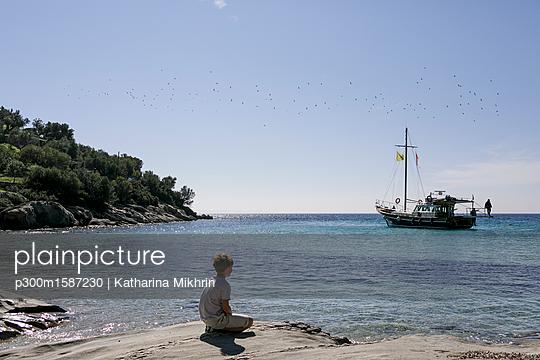 Boy sitting at seaside looking at view - p300m1587230 von Katharina Mikhrin