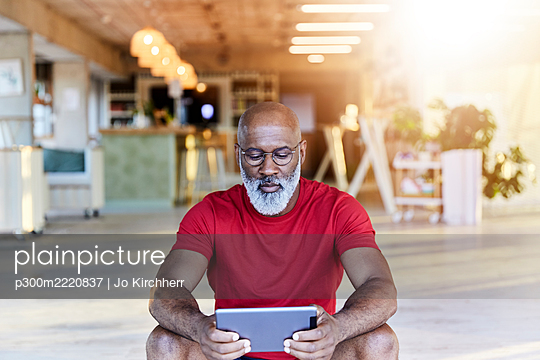 Mature man in red t-shirt using digital tablet while sitting at rooftop - p300m2220837 by Jo Kirchherr