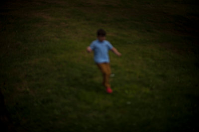 Blur picture of a boy running in the grass - p1007m1134863 by Tilby Vattard
