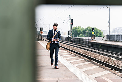 Businessman with cell phone walking at the platform - p300m2004749 by Uwe Umstätter