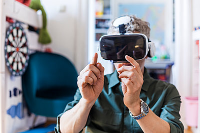 Portrait of mature man at home using Virtual Reality Glasses - p300m2030525 by Tom Chance